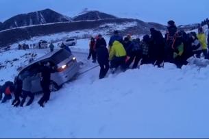 «Боулинг по-каракольски»: сноубордисты и лыжники вытащили съехавшую с дороги автомашину (видео)